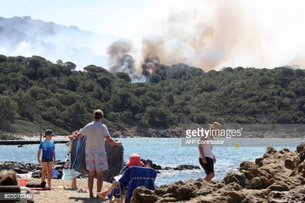 People enjoy the beach during a forest fire in La CroixValmer near SaintTropez on July 25 2017 as firefighters keep on battling blazes across...