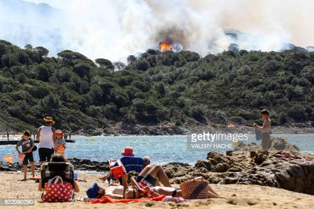 TOPSHOT People enjoy the beach during a forest fire in La CroixValmer near SaintTropez on July 25 2017 as firefighters keep on battling blazes across...