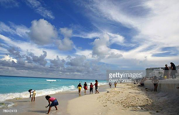 People enjoy the beach in Cancun state of Quintana Roo 19 August before the arrival of Hurricane Dean The monster hurricane began lashing Jamaica...