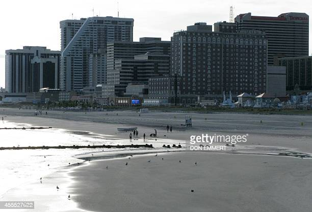 People enjoy the beach in front of casinos along the boardwalk September 15 2014 in Atlantic City New Jersey The Trump Plaza which opened on May 14...