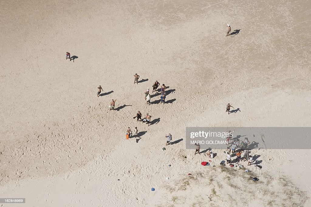 People enjoy the beach in Neptunia, about 20 km east of Montevideo, Uruguay, on February 27, 2013. AFP PHOTO/Mario Goldman
