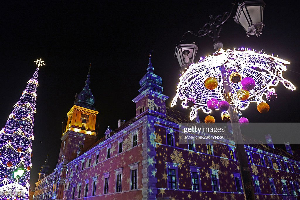 People enjoy the Christmas illuminations at the Royal Treaty street in Warsaw on December 1, 2012.