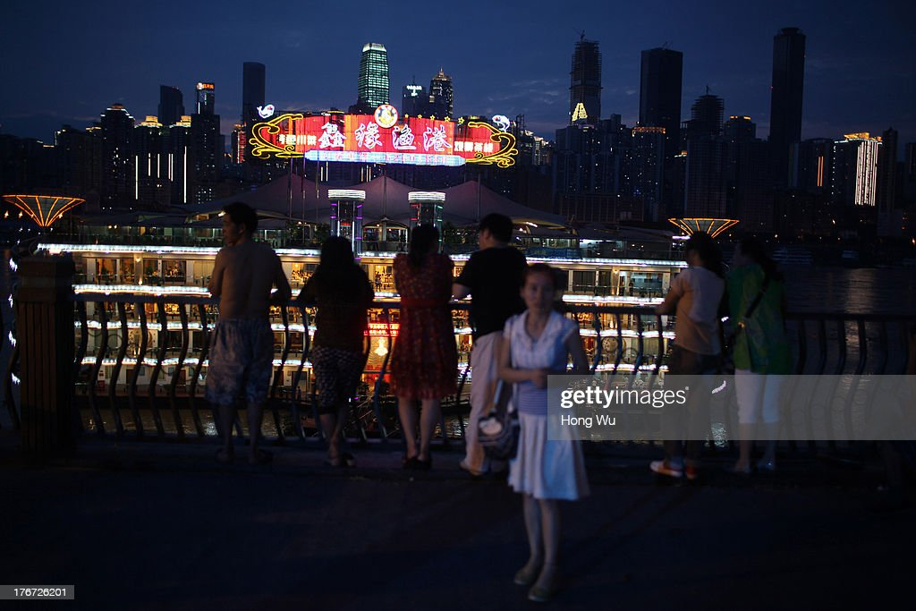 People enjoy the coolness in the night near by a luxurious boat restaurant along the Yangtze River on August 4, 2013 in Chongqing, China. Chongqing is a major city in southwest China and became the municipality was created on 14 March 1997. It known as a 'Mountain City' and 'River City' was constructed on the mountain and along the Yangtze River.