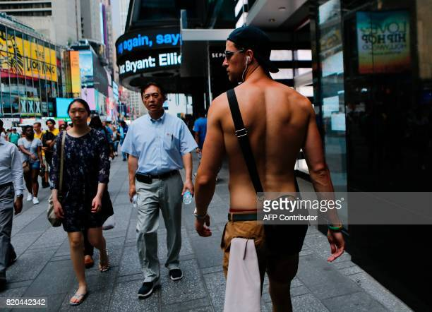 People enjoy the day at Times Square as hot temperatures continue in New York on July 21 2017 / AFP PHOTO / EDUARDO MUNOZ ALVAREZ