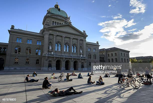 People enjoy the end of a warm autumn day next to the House of Swiss Parliament on October 17 2014 in Swiss Capital Bern AFP PHOTO / FABRICE COFFRINI