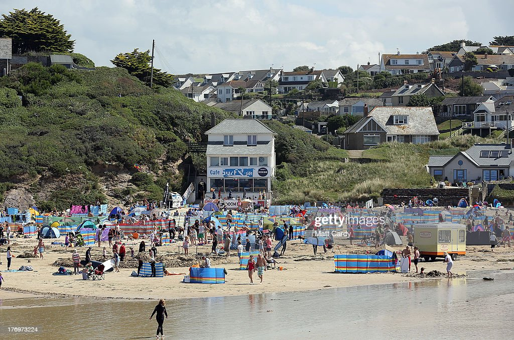 People enjoy the fine summer weather on the beach at Polzeath on August 20 2013 near Padstow England Polzeath is one of the closest beaches to the...