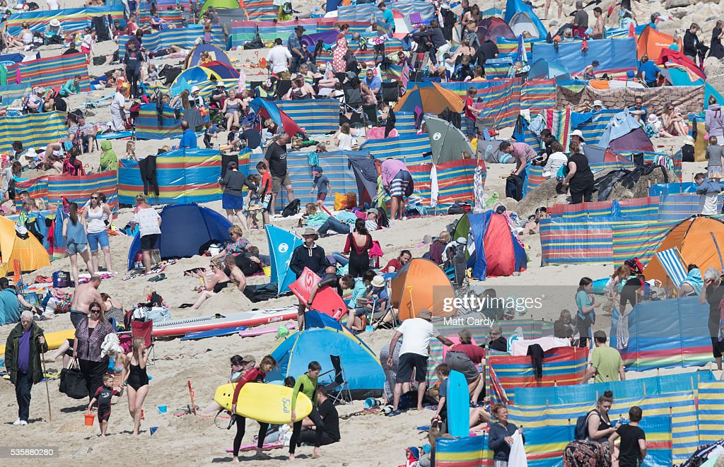 People enjoy the fine weather as they gather on the beach at Sennen Cove on May 30, 2016 in Cornwall, England. As some parts of the UK were bathed in sunshine for the bank holiday weather forecasters have warned that gale-force winds and thunderstorms will sweep in from the east overnight.