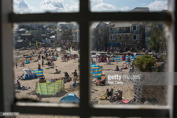 People enjoy the fine weather on the harbour beach viewed from inside the fisherman's chapel on August 4 2014 in St Ives Cornwall England A recent...