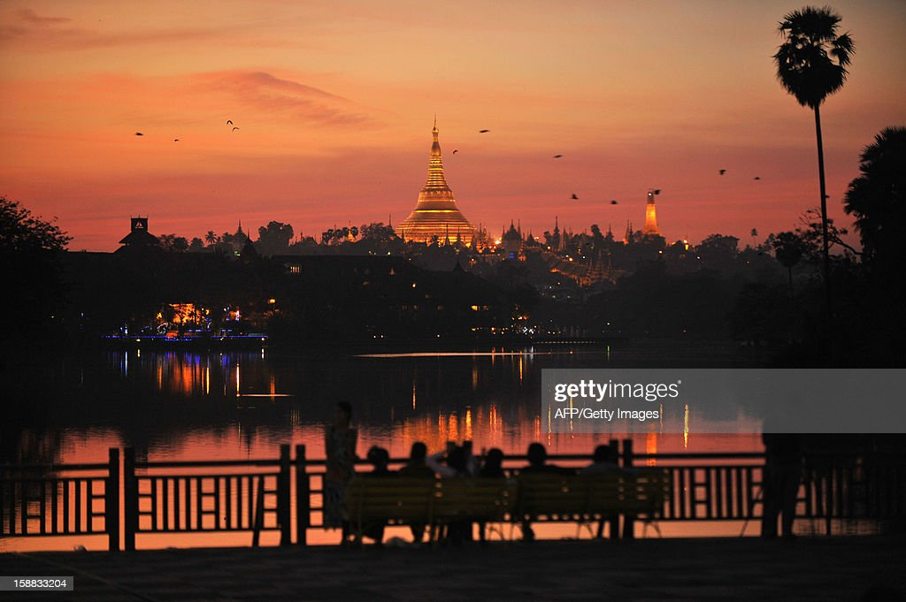 People enjoy the last sunset of 2012 at Kandawgyi Lake in Yangon on December 31, 2012. Some 50,000 people were expected to flock to the revered golden Shwedagon Pagoda in Yangon for the Myanmar city's first public countdown with fireworks, seen as further evidence of opening up after decades of junta rule. AFP PHOTO / Ye Aung Thu