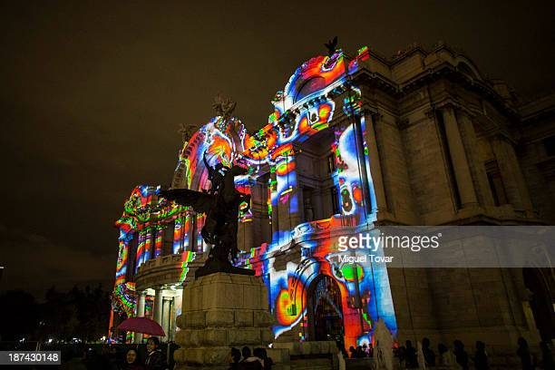 People enjoy the light show of FILUX International Lights Festival Mexico projected at the Palace of Fine Arts on November 08 2013 in Mexico City...
