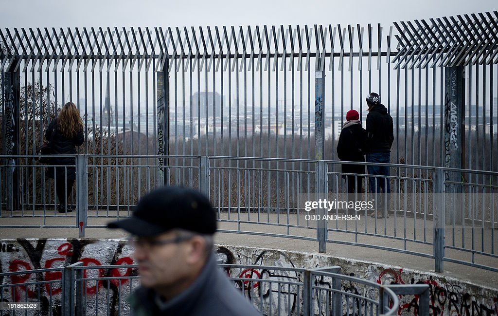 People enjoy the limited view from the top of the Humbolthain flak tower remains on a misty Sunday afternoon in Berlin on February 17, 2013. The concrete twin tower including a bunker was constructed during World War II, between 1941 and 1942, and partly blown up by French troops after the war. Nowadays, climbers use its remains to train their skills.