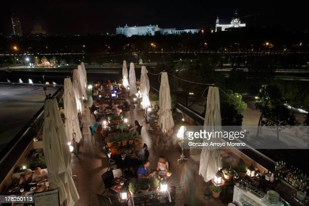 People enjoy the night at Cafe del Rio Roof Terrace at Madrid Rio promenade with a view of The Royal Palace on August 26 2013 in Madrid Spain Along...