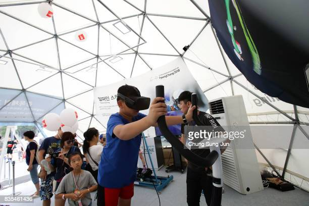 People enjoy the PyeongChang Winter Olympics booth next to 'Bobsleigh In the City' event on August 19 2017 in Seoul South Korea The 22metrehigh...