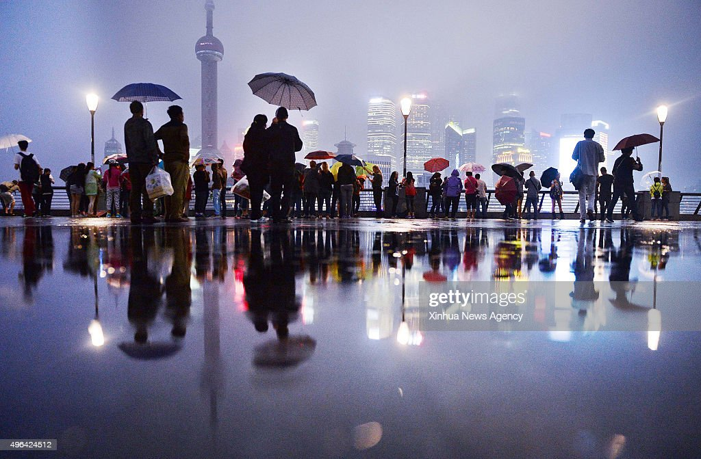 SHANGHAI SEPTEMBER 22 2015 People enjoy the scenery as their shadows are reflected in a puddle of water in the early morning at the Bund in Shanghai...