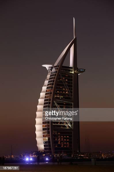 People enjoy the setting sun on the beach next to the luxury Burj Al Arab Hotel on November 13 2013 in Dubai United Arab Emirates Dubai is recovering...