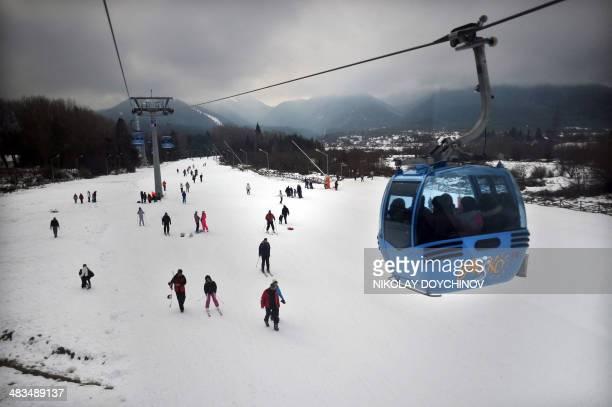 People enjoy the snow under a ski gondola ferrying up to Banderishka polyana ski resort near Bansko some 150 km south from Sofia on February 13 2014...