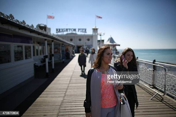 People enjoy the spring sunshine Brighton Pier on April 22 2015 in England Parts of the United Kingdom are experiencing warm sunny weather