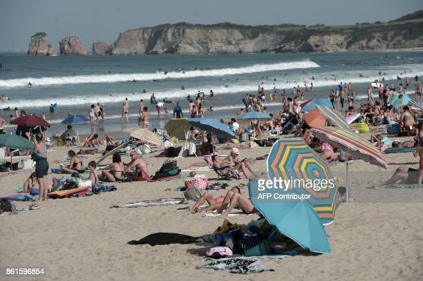 People enjoy the sun at the Grande Plage beach in Hendaye southwestern France on October 15 2017 as unusually warm autumnal temperatures reach 30...