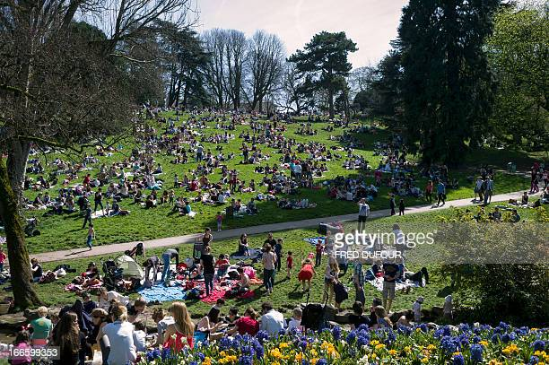 People enjoy the sun in the ButtesChaumont Park on April 2013 in Paris AFP PHOTO / FRED DUFOUR