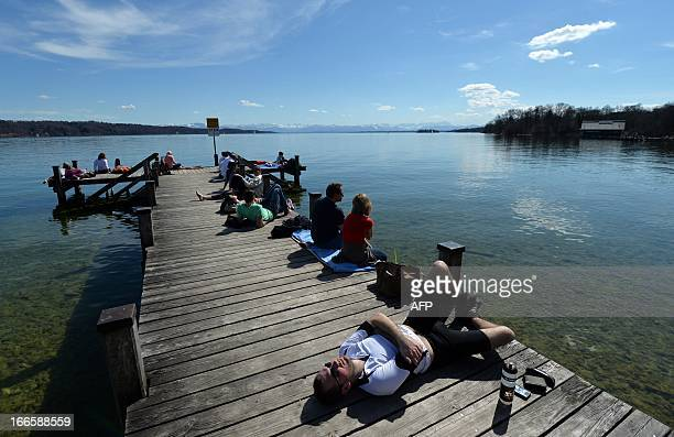 People enjoy the sun shine on a pier at Starnberger See southern Germany on April 14 2013 as temperatures rose to up to 20 degrees Celsius AFP PHOTO...