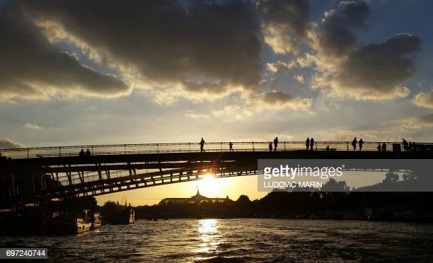 People enjoy the sunset on LeopoldSedarSenghor Bridge across the Seine River on June 17 2017 in Paris / AFP PHOTO / Ludovic MARIN