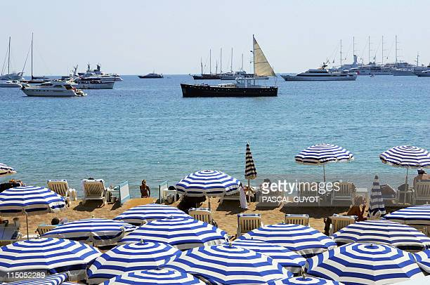 People enjoy the sunshine at the beach in Cannes 18 May 2004 during the 57th Cannes film festival in the French Riviera town With the Cannes party...