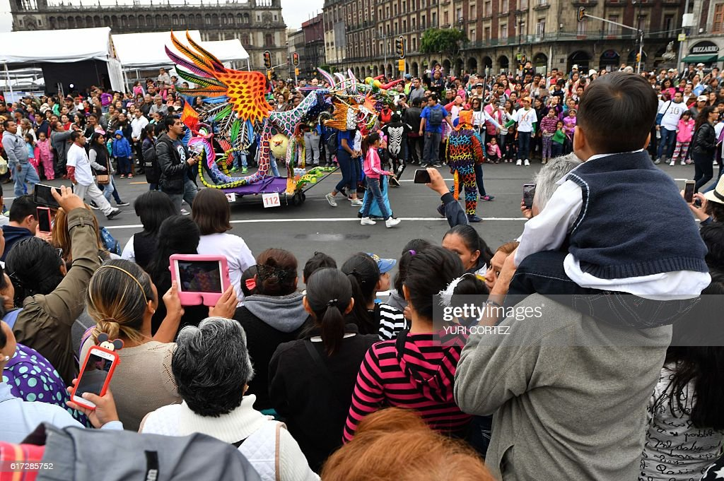 People enjoy the tenth Monumental 'Alebrijes' Parade and contest organized by the Folk Art Museum, on October 22, 2016 in Mexico City. More than two hundreds 'Alebrijes' -Mexican folk art traditional sculptures representing fantastical creatures - take part in the event. / AFP / YURI