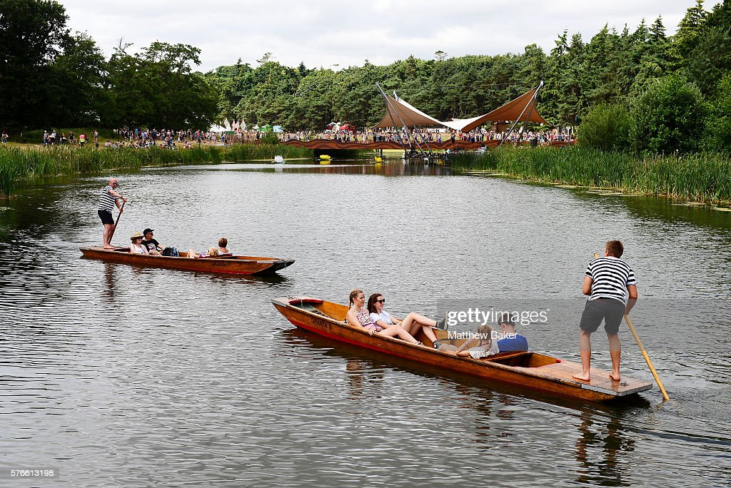 People enjoy the warm weather during a punt ride at Latitude Festival at Henham Park Estate on July 16 2016 in Southwold England