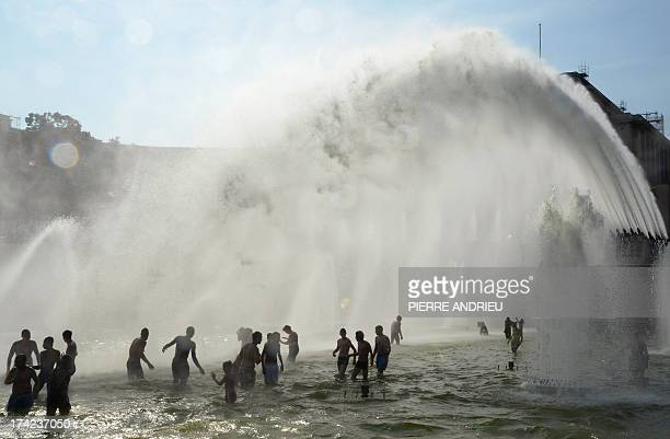 People enjoy the water of a fountain near the Trocadero on a warm summer day in Paris on July 22 2013 AFP PHOTO PIERRE ANDRIEU2