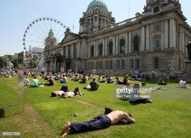 People enjoy their lunchtime in the grounds of City Hall in Belfast
