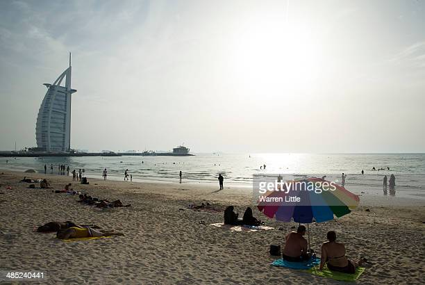 People enjoy Umm Suqeim Beach near the luxury Burj Al Arab Hotel on April 17 2014 in Dubai United Arab Emirates