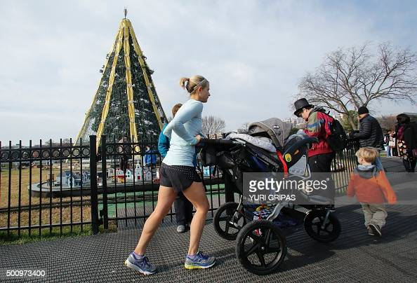 People enjoy unusual warm weather near the National Christmas tree in Washington DC on December 11 2015 Temperatures in the US capital are expected...