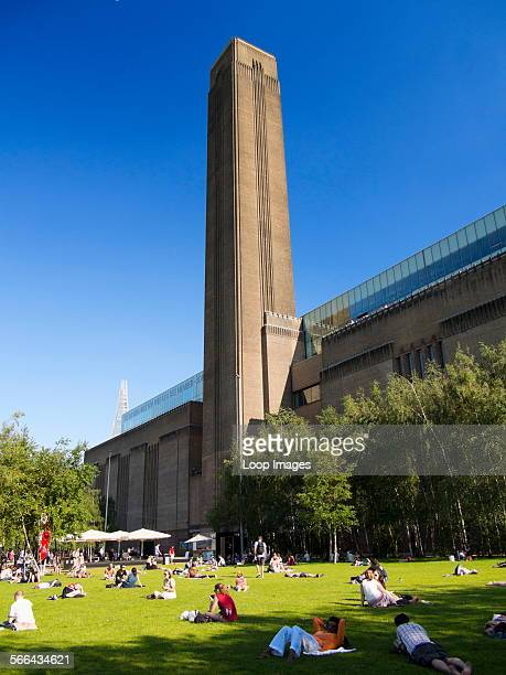 People enjoying a summer day in front of the Tate Modern gallery in London