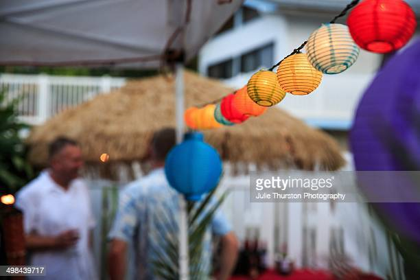 People Enjoying an Outdoor Hawaiian Garden Party with Grass Umbrella and Colorful Hanging Ball Lantern Lights