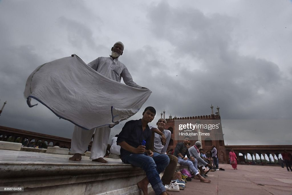 People enjoying at Jama Masjid during the rain, on August 19, 2017 in New Delhi, India. Delhi received showers early morning which brought temperatures down to a comfortable 26 degrees Celsius. The India Meteorological Department (Met) officials said that there might be thunderstorm with showers later in the day while the maximum temperature is likely to be around 34 degrees Celsius.