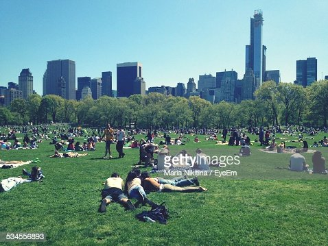 People Enjoying At Park Against Modern Building In City