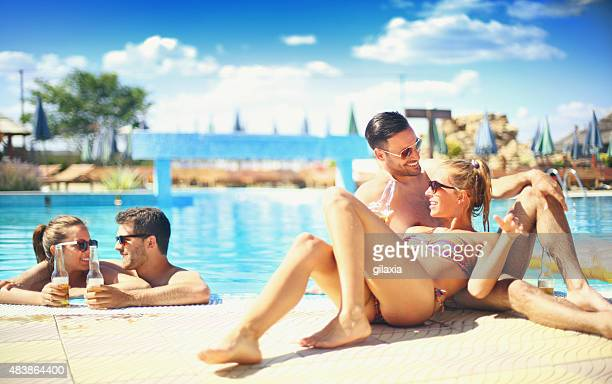 Gens profitant de boissons au bord de la piscine.