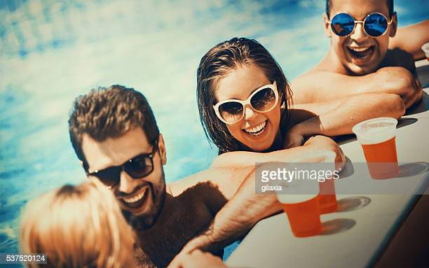Persone godendo drink a bordo piscina.