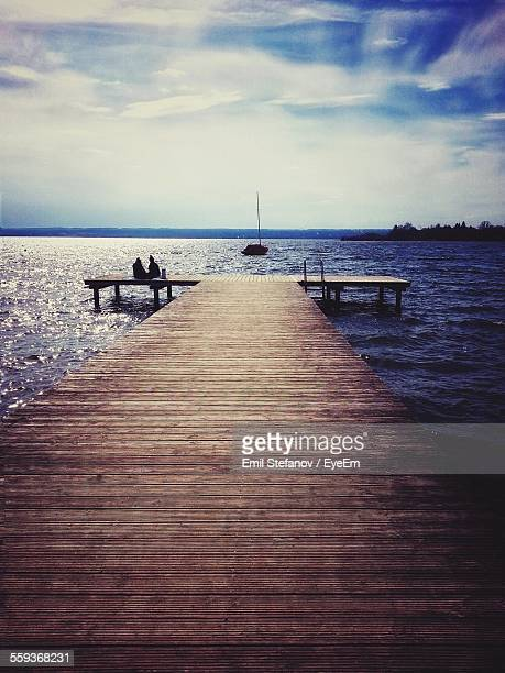 People Enjoying On Ammersee Lake Jetty Against Blue Sky