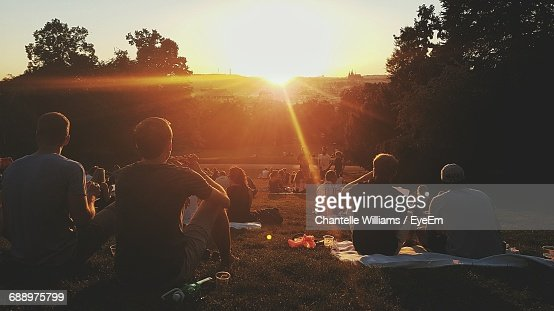 People Enjoying On Field In Park During Sunset