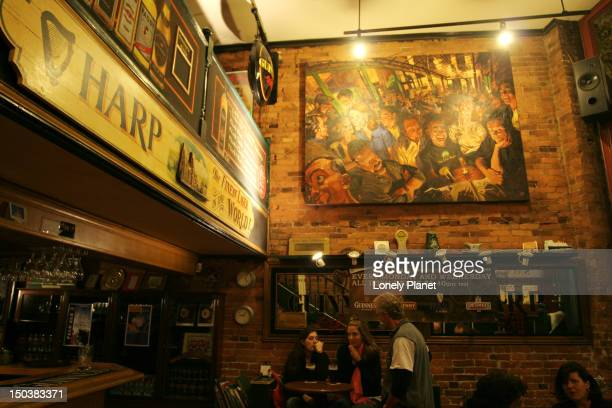 People enjoying pints in traditional atmosphere of Irish Heather pub.