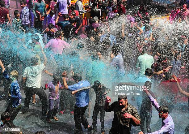 People enjoying rain of coloured water during Holi celebration organised by Hindu Utsav Samiti at Peer Gate on March 6 2015 in Bhopal India Festival...