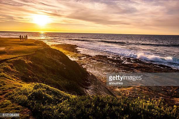 Pessoas beneficiando pôr do sol na praia de La Jolla, Califórnia, EUA