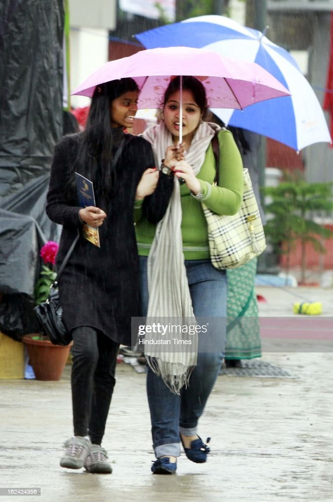 People enjoying the rainfall on February 23, 2013 in New Delhi, India.