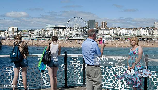 People enjoying themselves on Brighton Pier on the south coast during hot weather on July 20th 2013 Britain has been experiencing hot weather this...