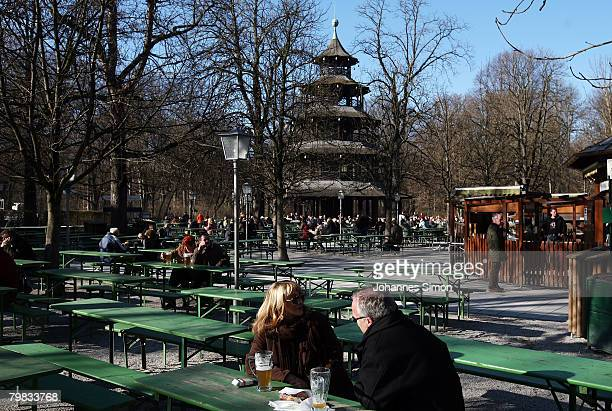 People enjoys sitting in the beer garden in front of Chinesischer Turm in the English Garden on February 19 2008 in Munich Germany Germany...