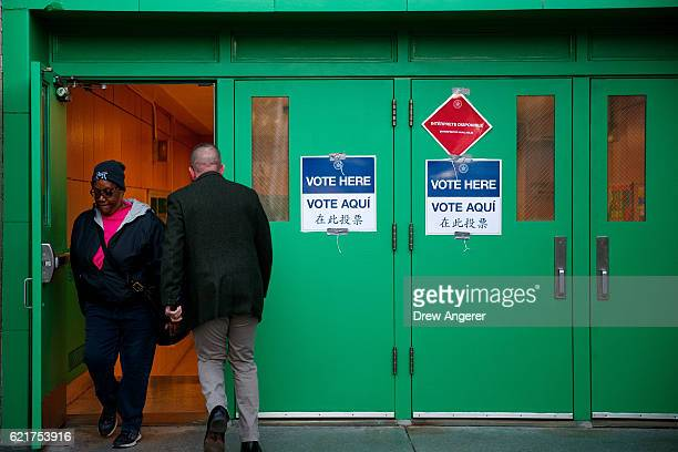 People enter and exit a polling site at Public School 261 November 8 2016 in New York City Citizens of the United States will choose between...