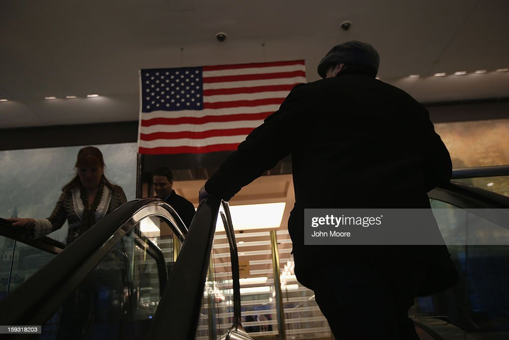 People enter and leave the American Express headquarters on January 11, 2013 in New York, New York. Following low fourth quarter earnings, the credit card giant announced plans to cut 5,400 jobs in the coming year.