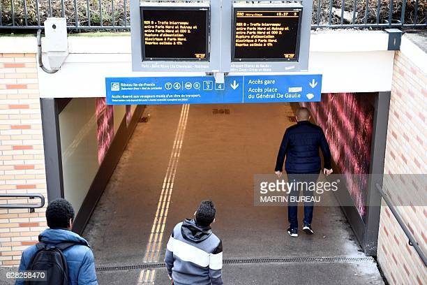 People enter in a tunnel under two monitor screens alerting of the interuption of the railway trafic due to a catenary pullout on December 7 2016 at...