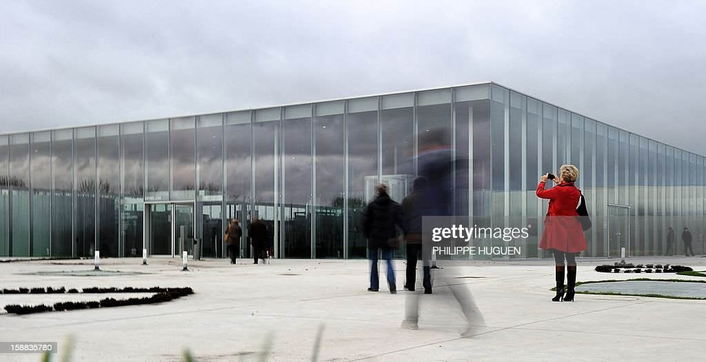 People enter the Louvre-Lens museum on December 31, 2012 in Lens, northern France. Three weeks after its inauguration, the museum welcomed its 100.000th visitor on December 28, 2012. AFP PHOTO PHILIPPE HUGUEN
